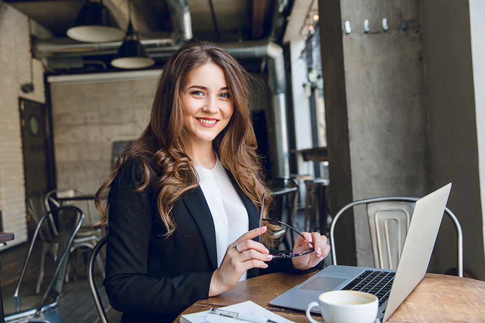 Widely smiling businesswoman working on laptop sitting in a cafe. Woman with long hair wears black jacket and white blouse and holds black eyeglasses in hands.